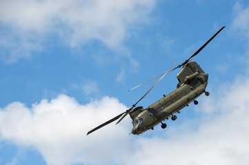 military cargo helicopter in a steep flight maneuver
