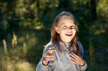 Attractive portrait of smiling little girl with mushroom