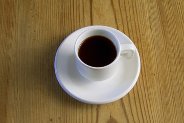 Close up of cup of espresso coffee on old wooden table