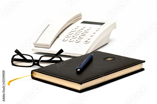 Telephone, glasses, agenda and pen isolated on white