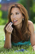 Beautiful Woman Outside Eating Blueberries and Smiling