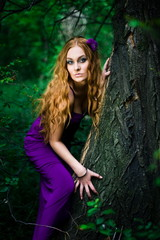 Redhead girl in forest in purple dress