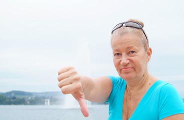 Unzufriedene ältere Frau zeigt finger nach unten. Sample text.