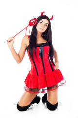 sexy brunette girl sits, dressed in Halloween costume imp