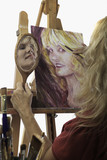 blond female artist in her fifties painting self portrait