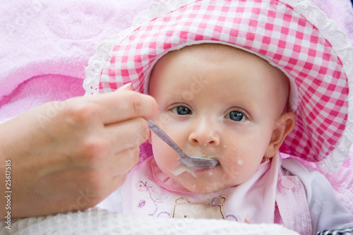 baby is fed from a spoon
