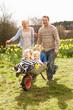 Father Giving Children Ride In Wheelbarrow Through Field Of Spri