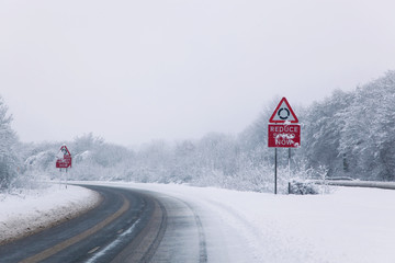 Road with Reduce speed now sign during snow fall