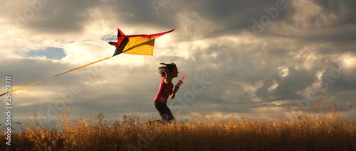 Leinwanddruck Bild Girl flying a kite.