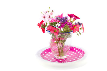 lovely garden bouquet in a glass vase on a pink dotted plate iso