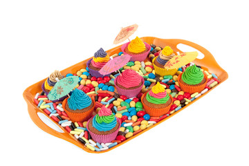 a tray full of colorful creamed cupcakes with umbrella's between