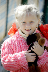 Smiling girl with toy dog
