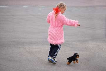 Little girl playing with the toy dog