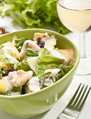 traditional caesar salad with a glass of white wine