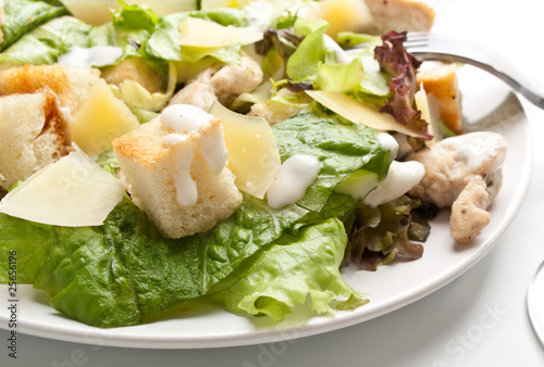 traditional caesar salad on white plate with a fork