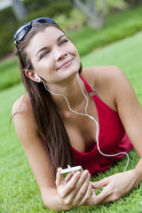 Beautiful Brunette Woman laying Down Listening to MP3 Player