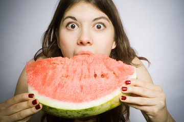 Portrait of the girl with a segment of a ripe water-melon.