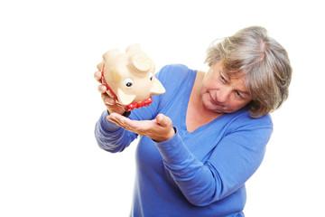 Seniorin mit leerem Sparschwein