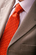 Detail of perfect business man grey suit with red tie.