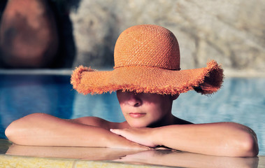 Attractive young woman in hat resting by the side of a pool
