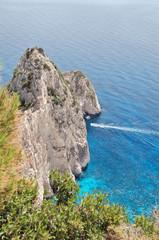 Small boat cruising through rocks. Zakynthos, Greece.
