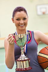 Young woman holding a trophee and a basket ball