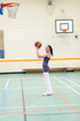 Concentrated woman practicing basketball