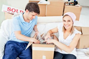 Joyful caucasian couple unpacking boxes with glasses