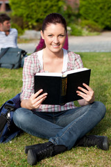 Serious female student reading a book sitting on grass