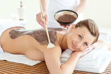 Delighted caucasian woman receiving a beauty treatment with mud