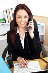 Self-assured businesswoman talking on phone and using her laptop