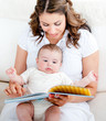 Loving mother reading a story to her adorable baby sitting on th