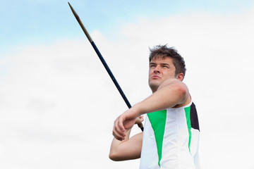 Determined sportsman throwing the javelin