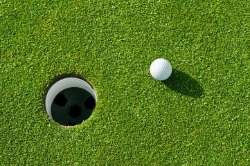 Golfball vor Loch