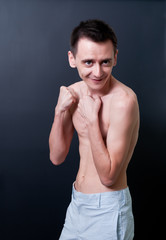 Skinny topless man showing his muscles
