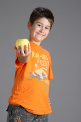 a boy holding and offering a apple