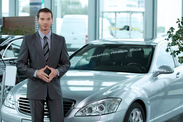 Portrait of car salesperson standing in car showroom