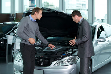 Car salesperson explaining about car's engine to customer