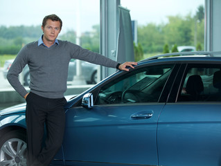 Portrait of young man standing by new car