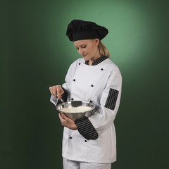 Young professional cook on green background - square