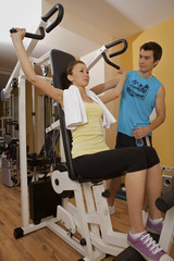 A young woman exercising with a personal trainer