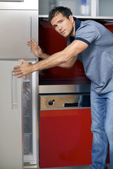 Portrait of young man opening door of refrigerator