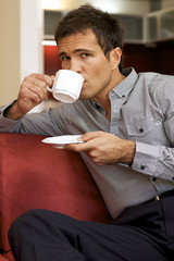 Portrait of young man drinking tea, sitting in sofa