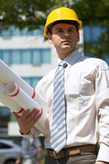 Architect in hardhat holding blueprint at construction site