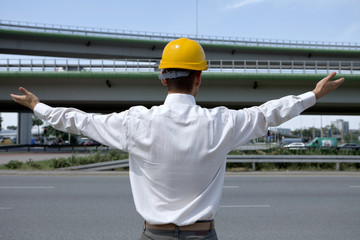 Architect in hardhat with arm raised at construction site