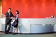 car salesman standing with female customer in showroom