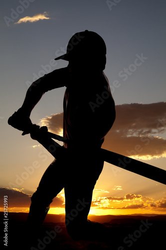 Silhouette baseball swing beginning sunset