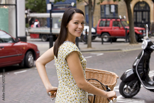 A young woman pushing her bicycle in the street