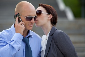 Businessman talking on phone by businesswoman