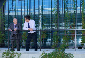 Businessmen in conversation by railing